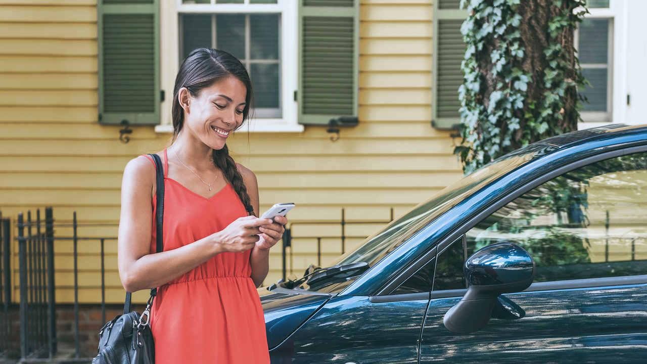 mulher mexe no celular depois de estacionar seu carro na Zona Azul Digital