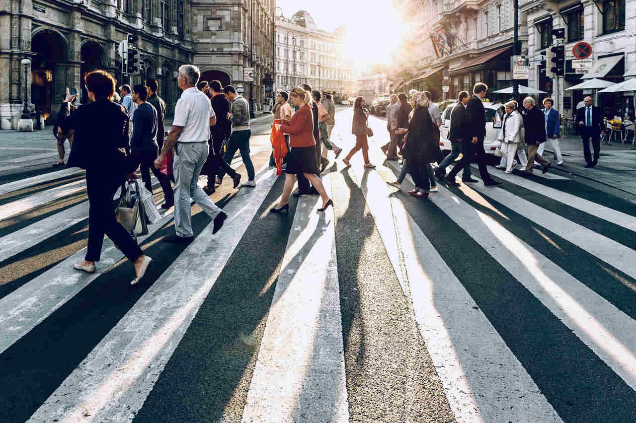 pessoas atravessam avenida em faixa de pedestres