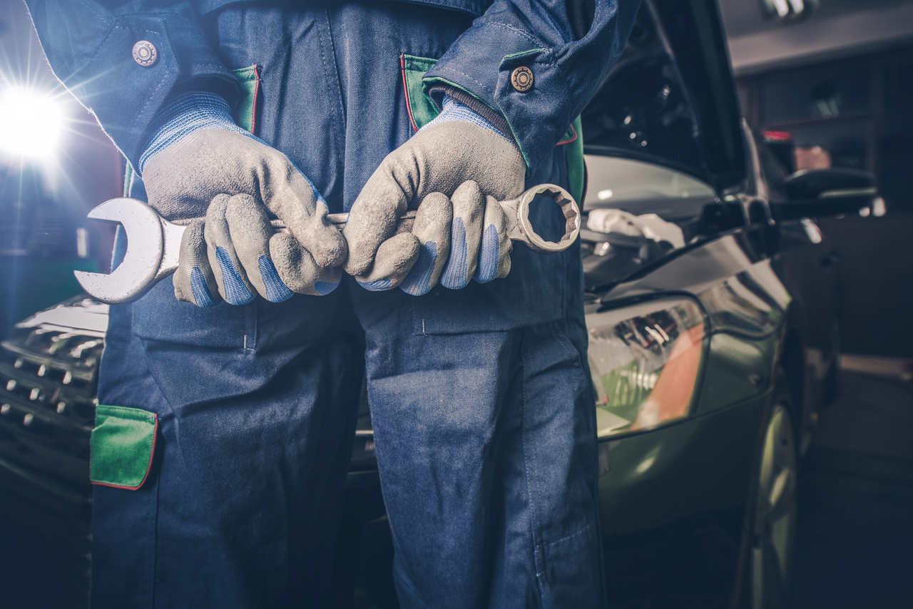 mecanico segura chave de fenda em frente a um carro na oficina