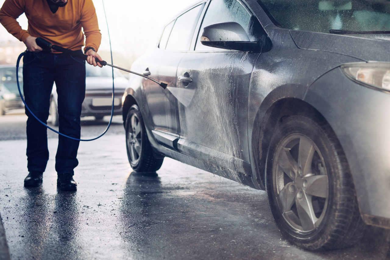 motorista joga jato de agua em carro ensaboado