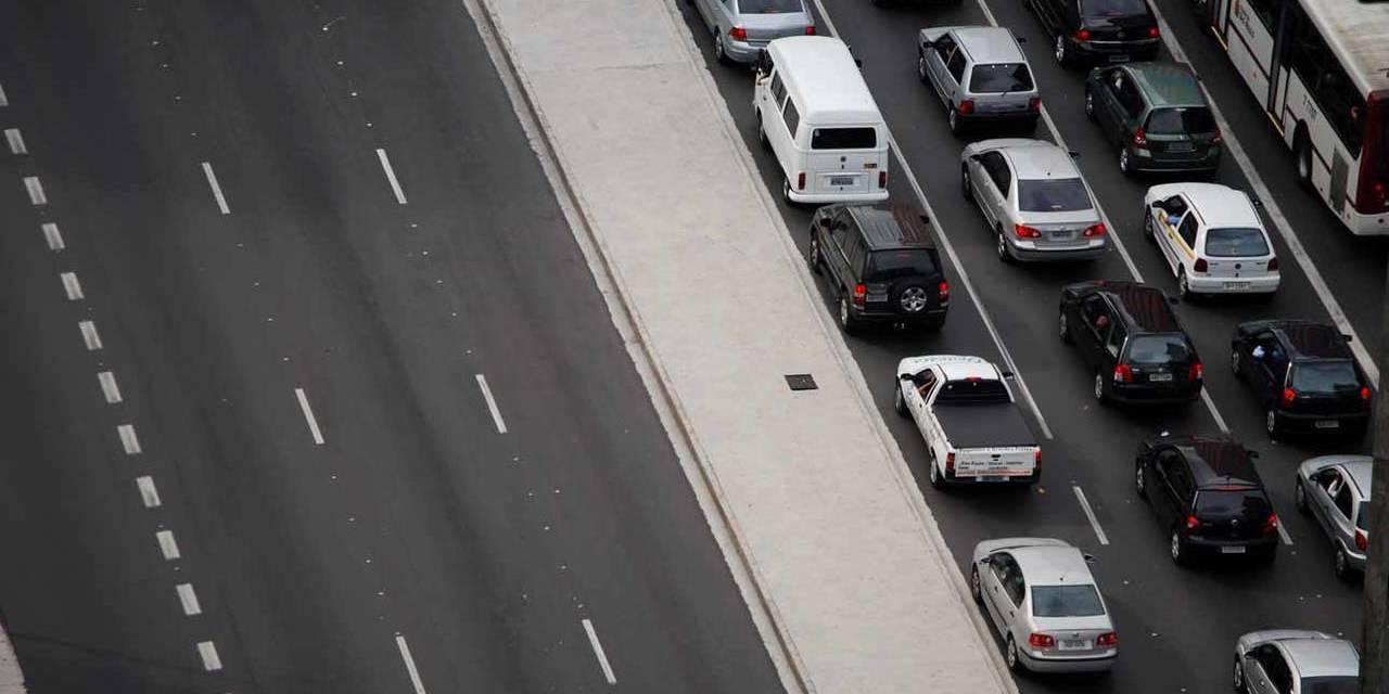 foto de avenida com um lado vazio e com outro lado congestionada por carros