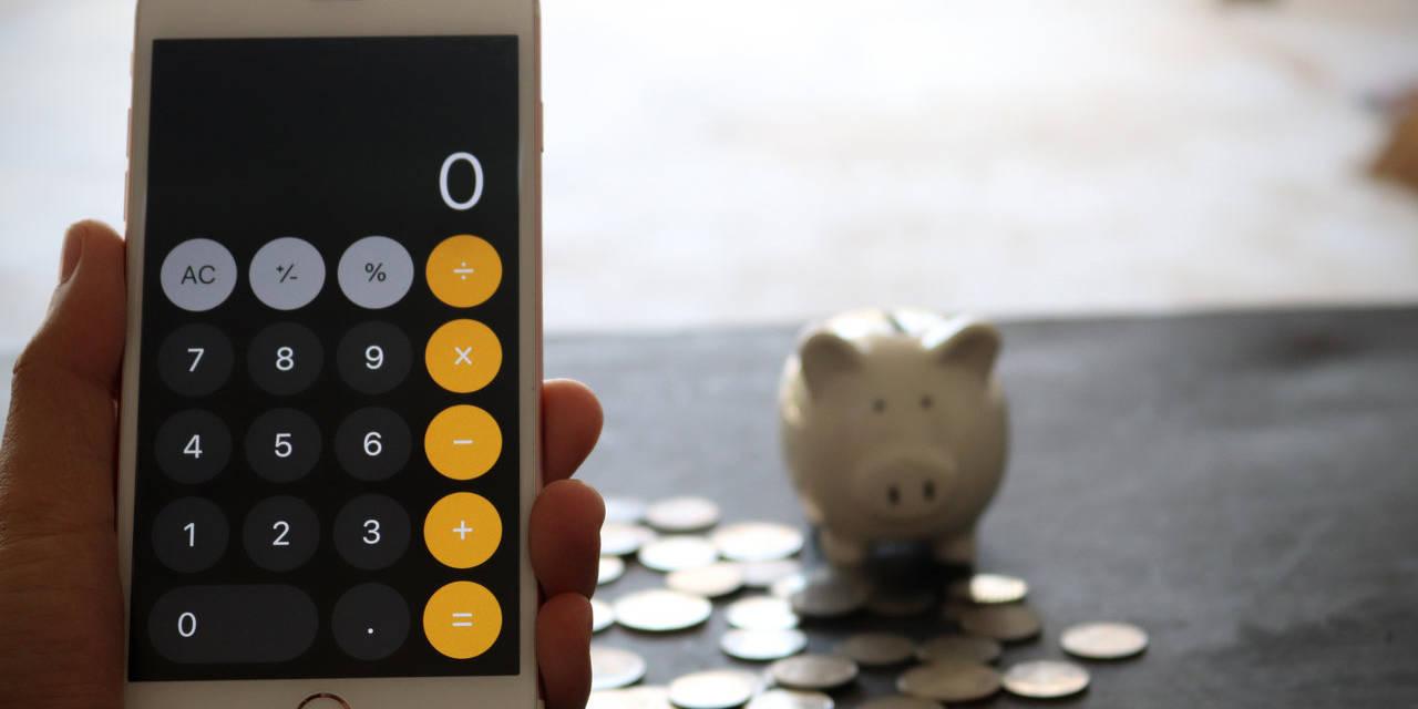 iphone em calculadora com cofre de porquinho e moedas ao fundo
