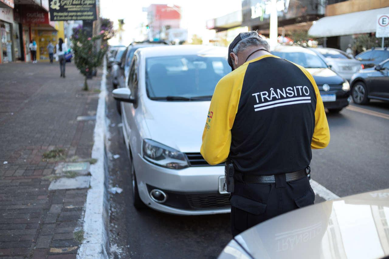 agente de transito multa carro estacionado em local proibido