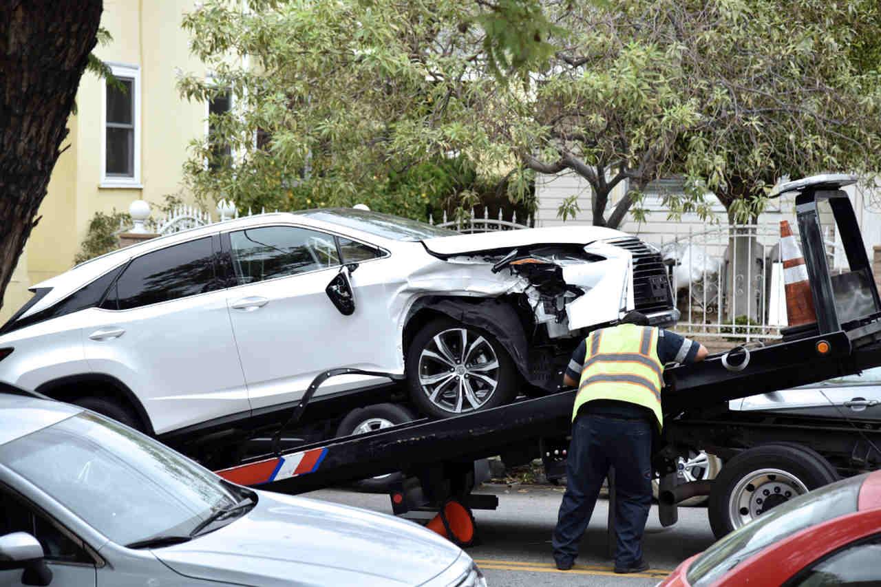 carro batido é guinchado por funcionario de seguradora