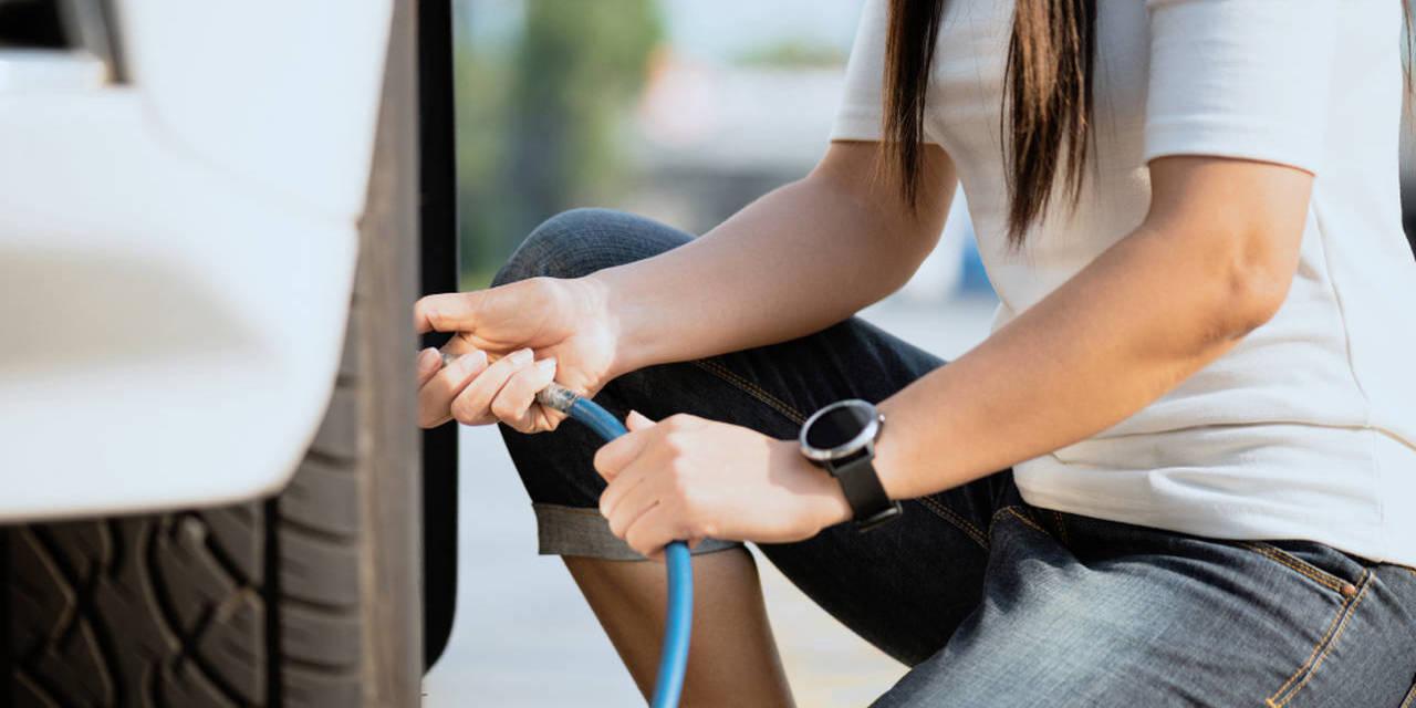 mulher calibra pneus do carro manutencao preventiva