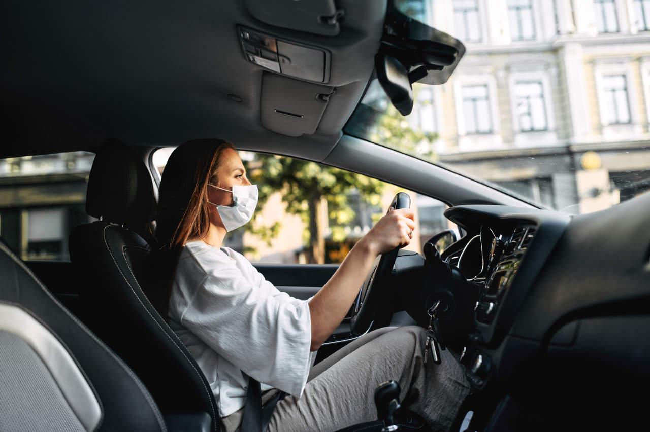 mulher com mascara branca dirige carro