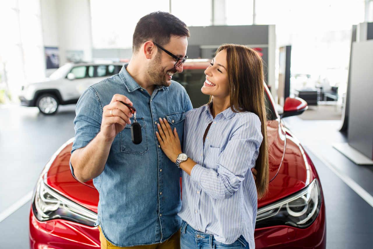 casal sorri um para o outro com a compra de um novo carro