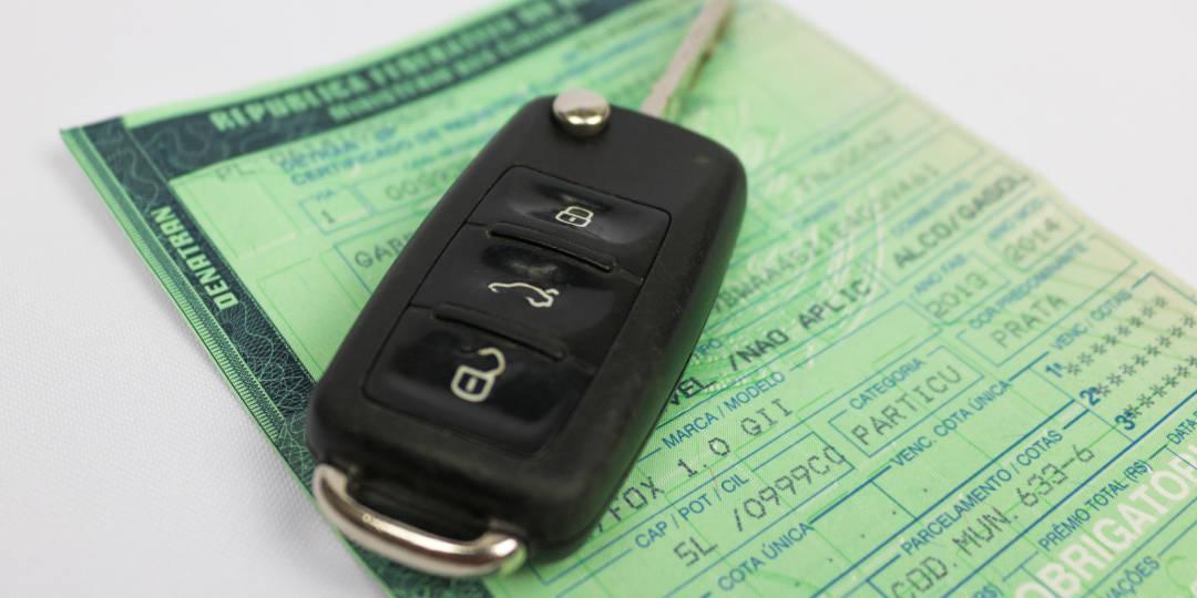 chave do carro em cima do documento do carro crlv