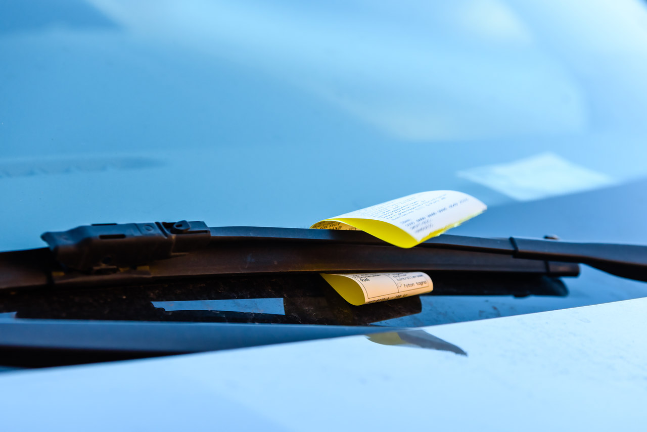 ticket de multa zona azul estacionamento rotativo no painel do carro preso pelo retrovisor