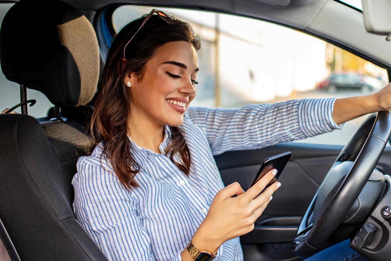 Mulher mexe no celular dentro do carro
