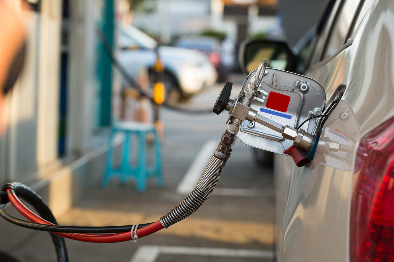 carro a gnv sendo abastecio em posto de combustível