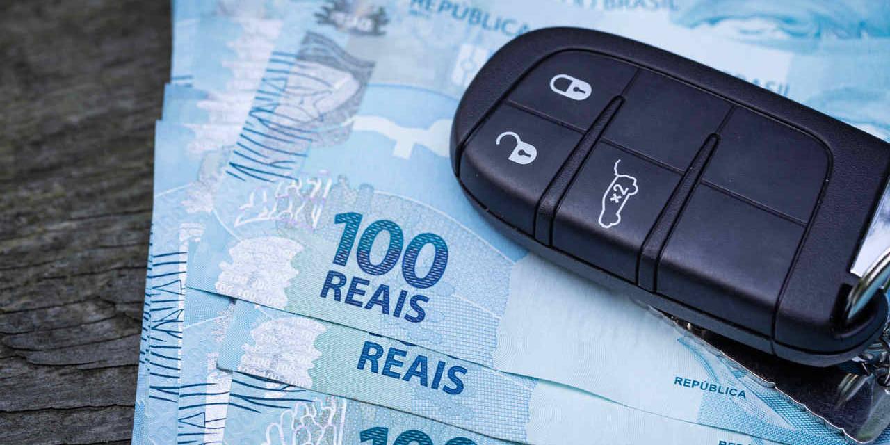 chave de carro sobre notas de cem reais
