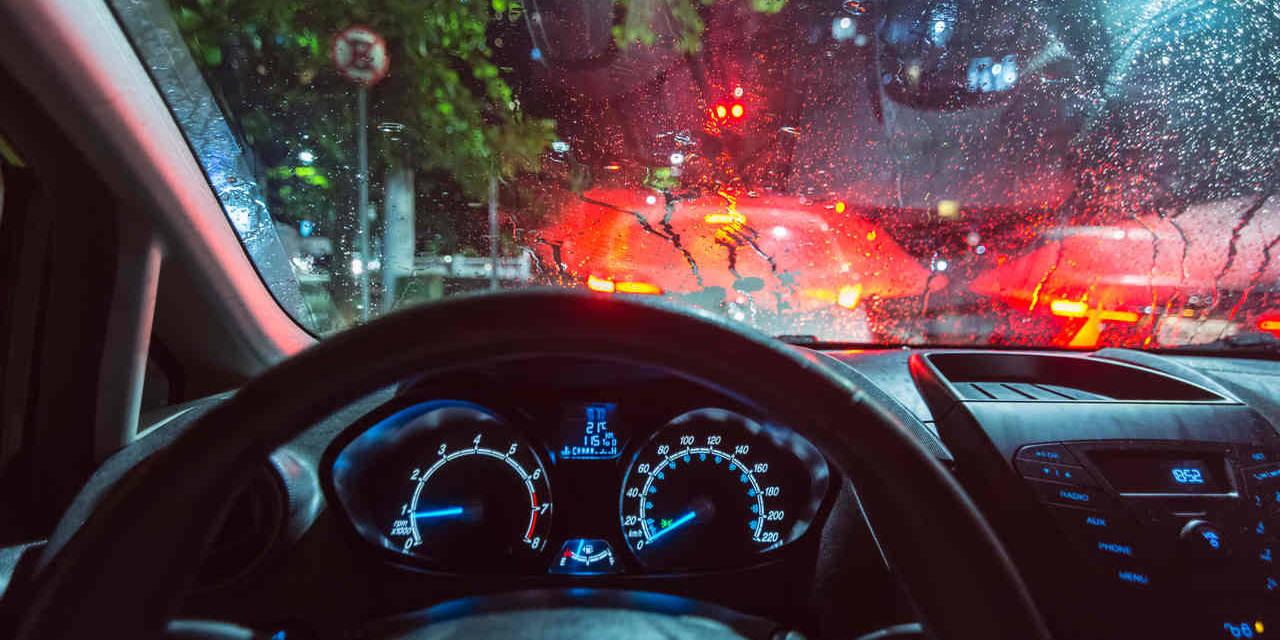 foto interna do ponto de vista do motorista no transito em dia de chuva