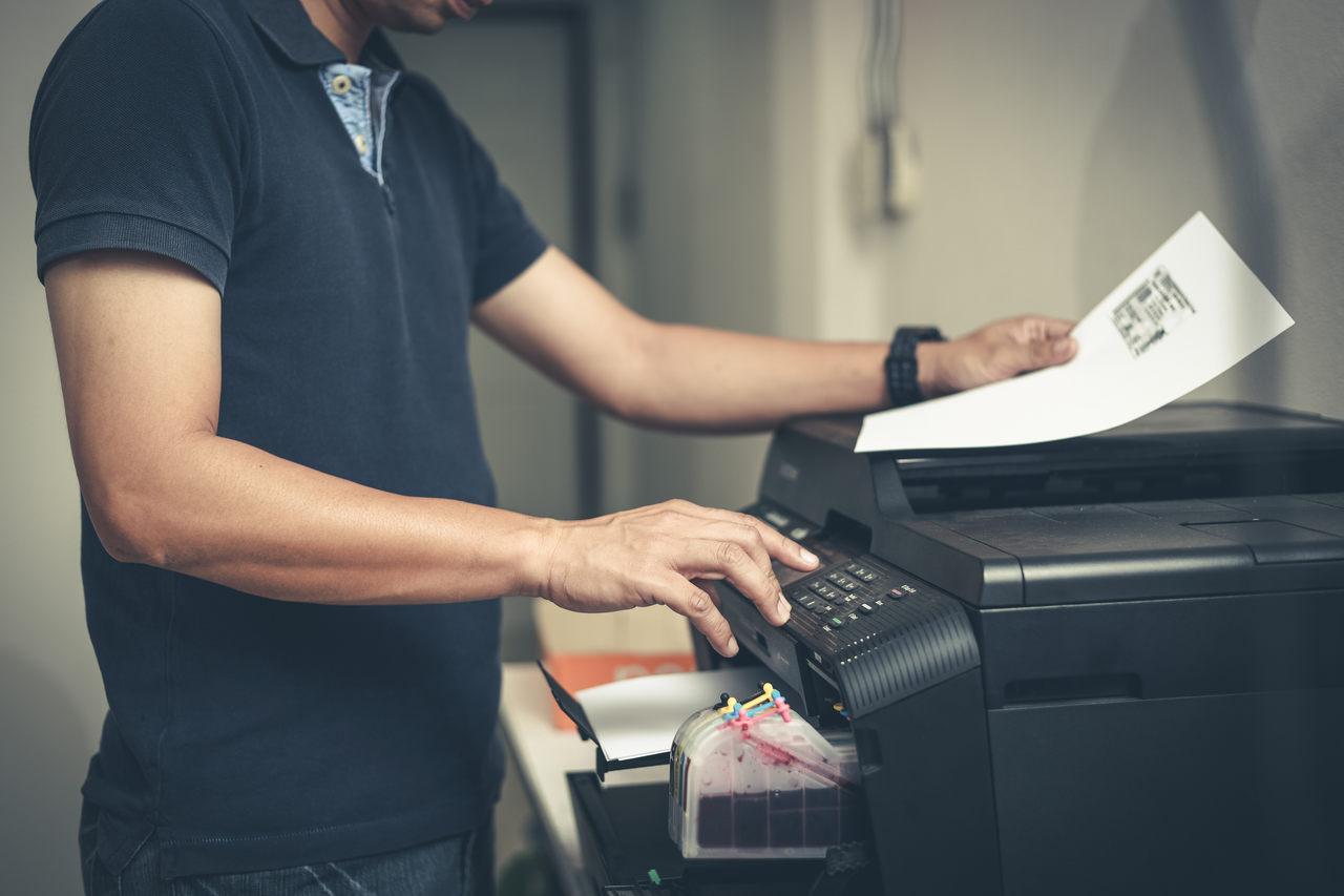 homem utiliza impressora para imprimir documento