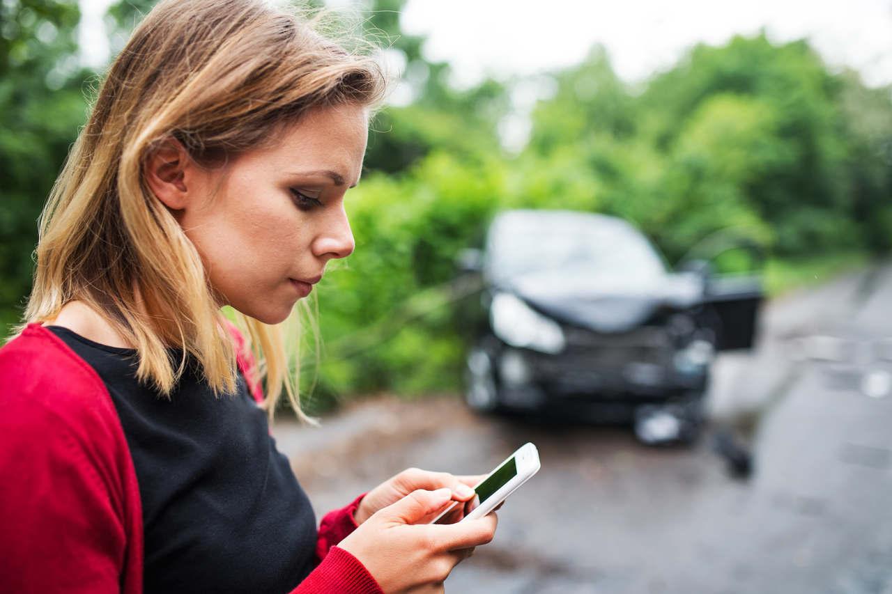 mulher preocupada com celular na mão e carro batido ao fundo