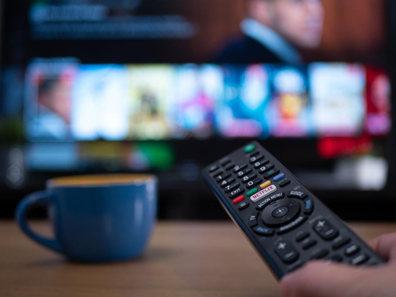 controle de televisão ao lado de xícara de café apoiada na mesa televisao ao fundo