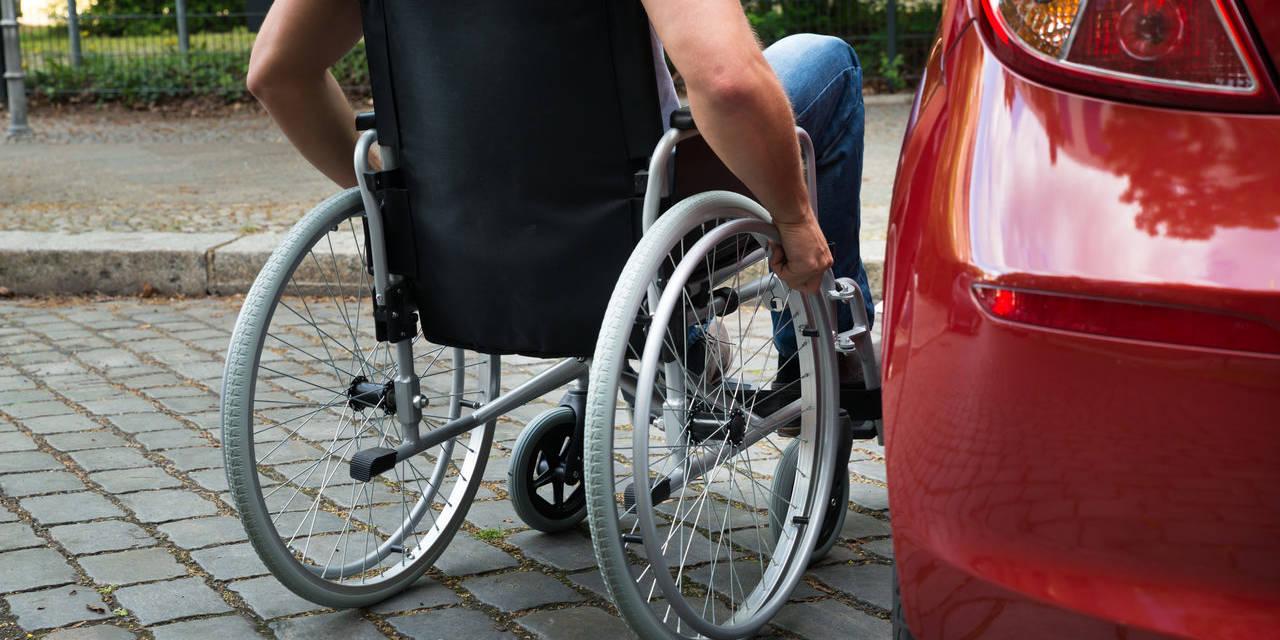 motorista sentado em cadeira de rodas ao lado do carro estacionado