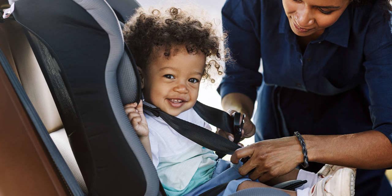 mãe coloca o cinto de segurança em seu filho na cadeirinha de carro