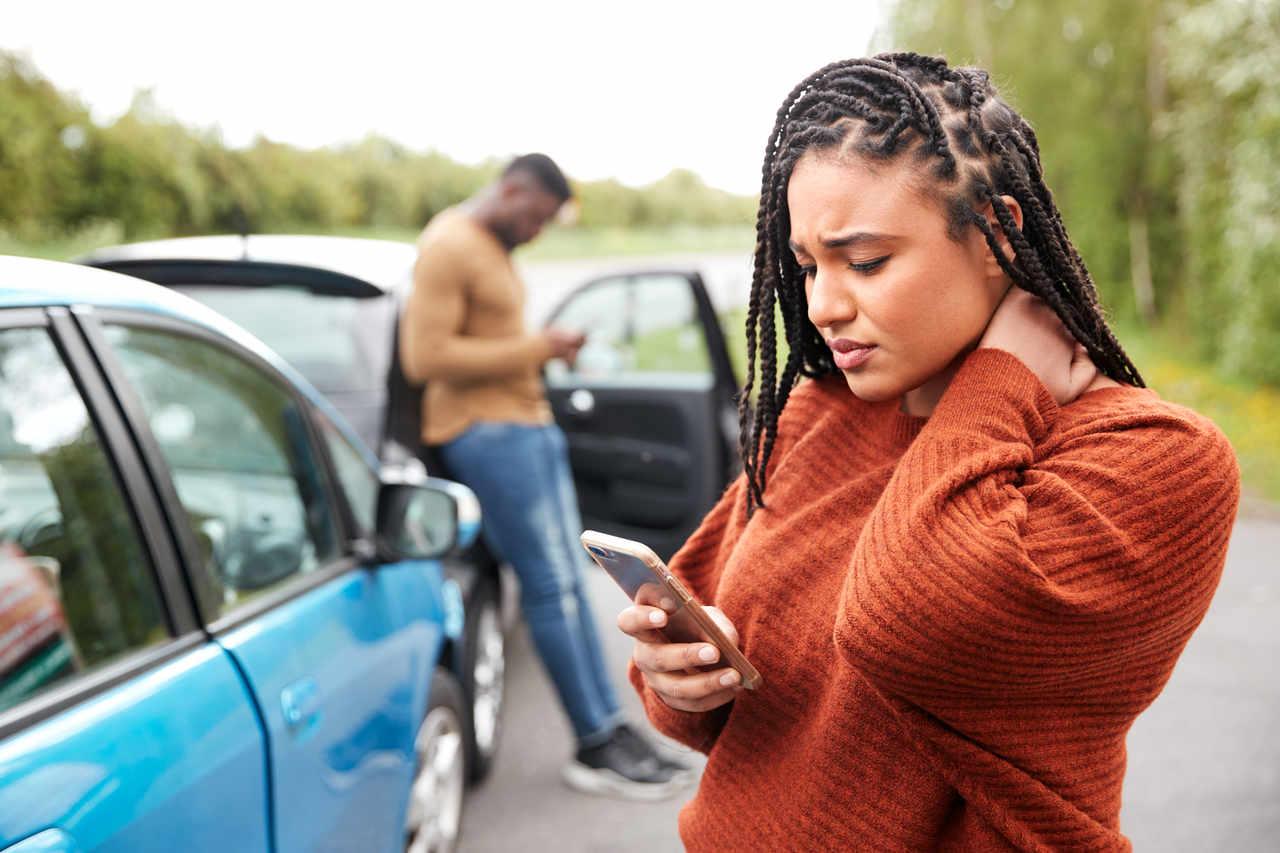 mulher mexe no celular após bater o carro em rodovia