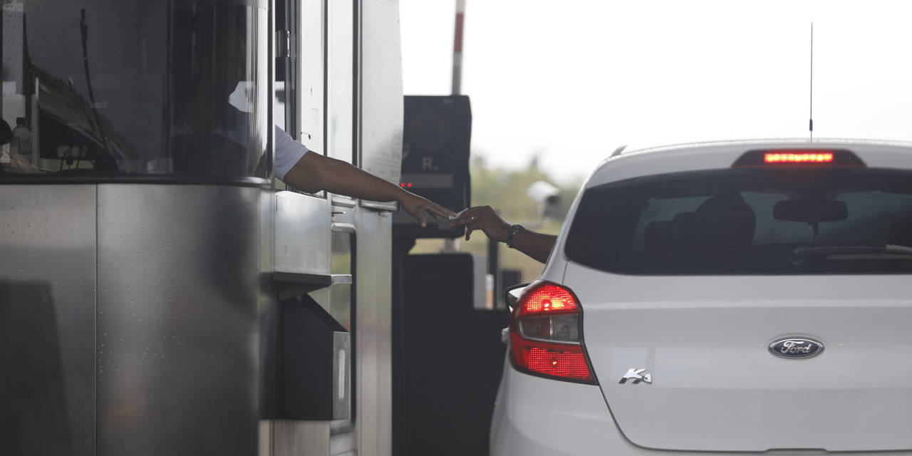 motorista pagando pedagio na cabine