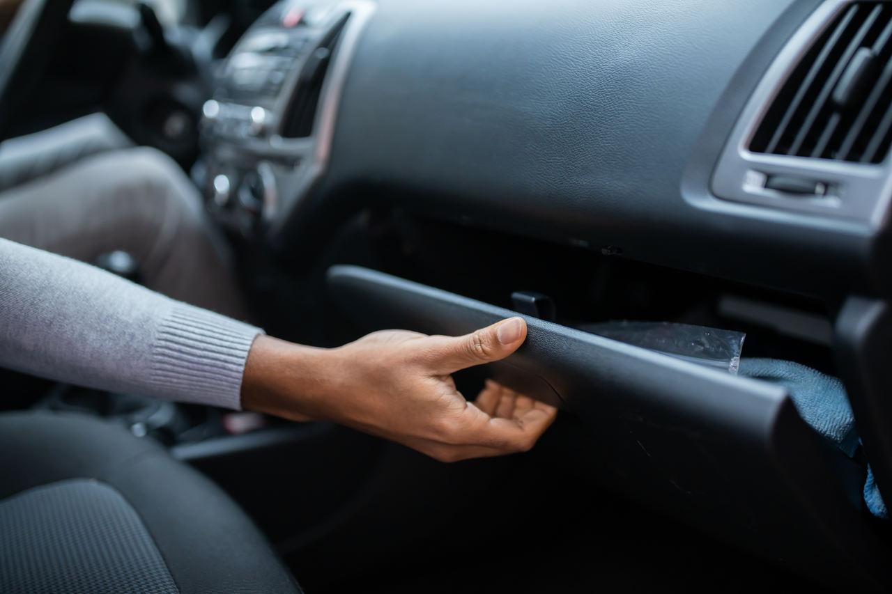 mulher abre o porta luvas do carro