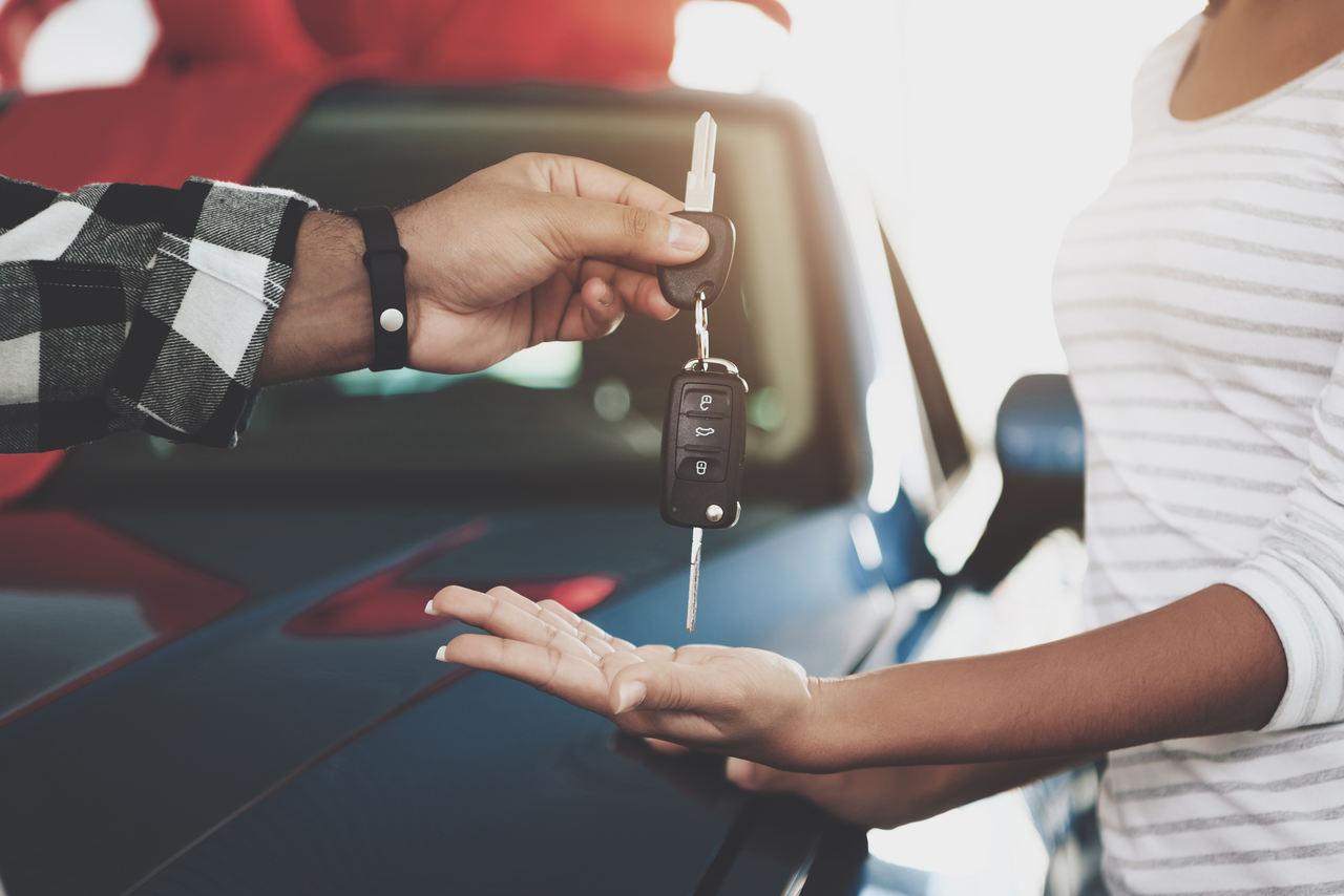 homem entrega chave do carro para nova proprietária após transferência de veículo