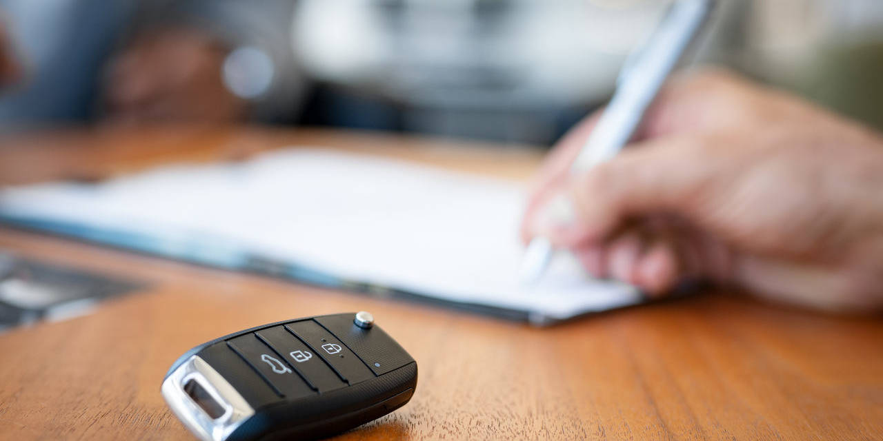 motorista assina documento do carro com canete enquanto chave esta sobre a mesa