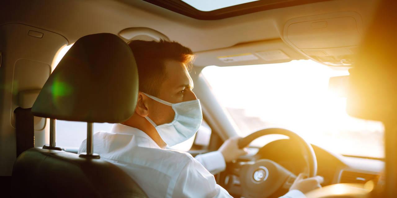 motorista de aplicativo no volante do carro usando mascara