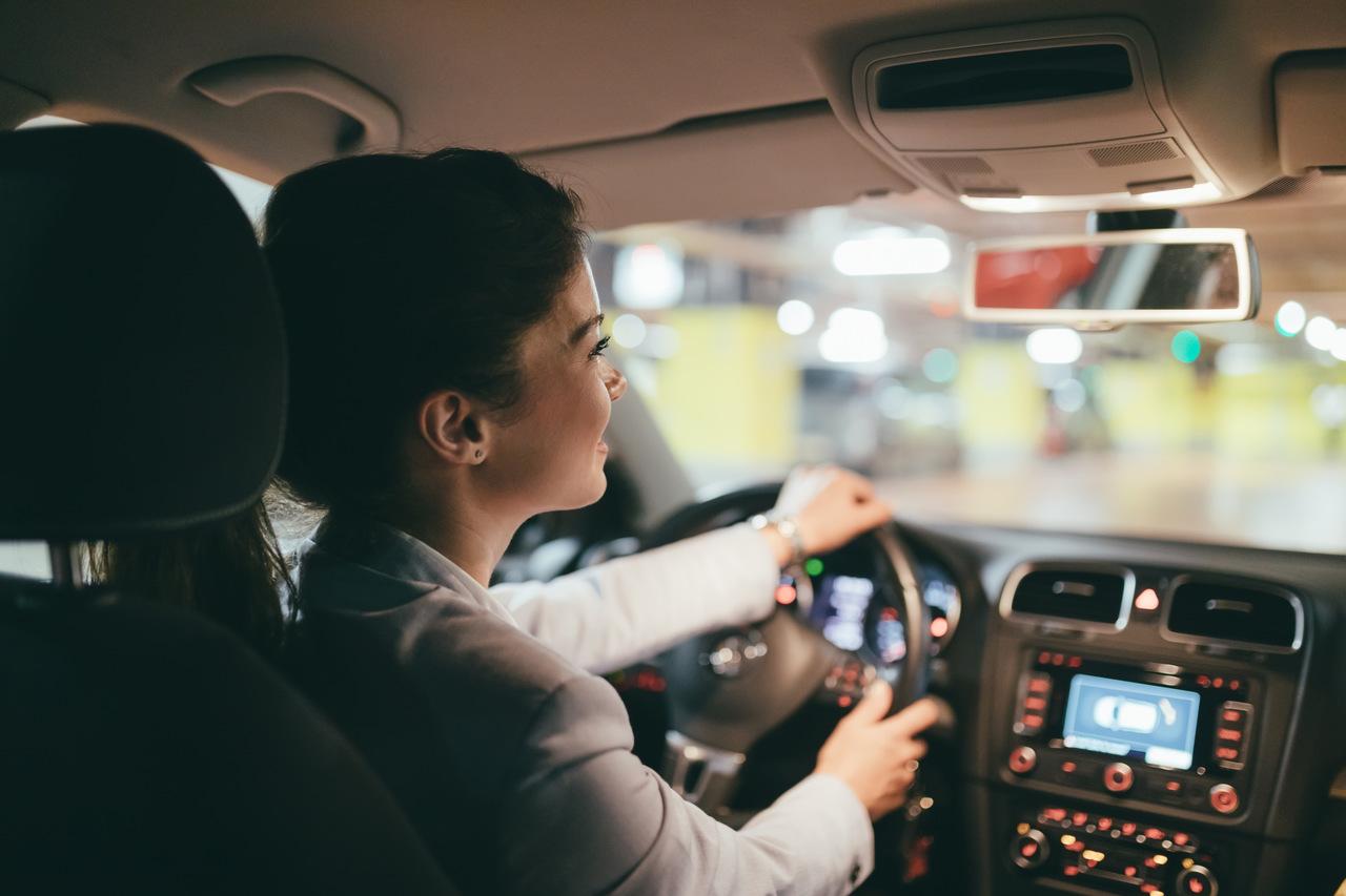 mulher dirige carro em estacionamento de shopping