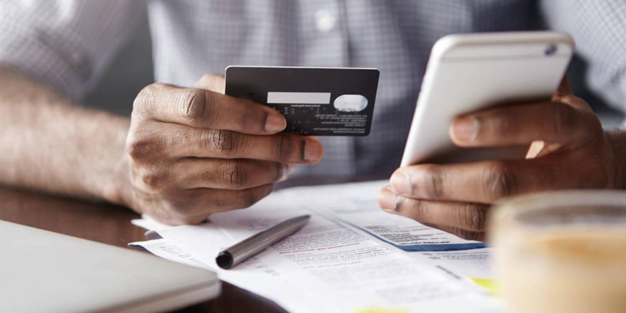homem segura celular e cartão de crédito para pagar ipva parcelado