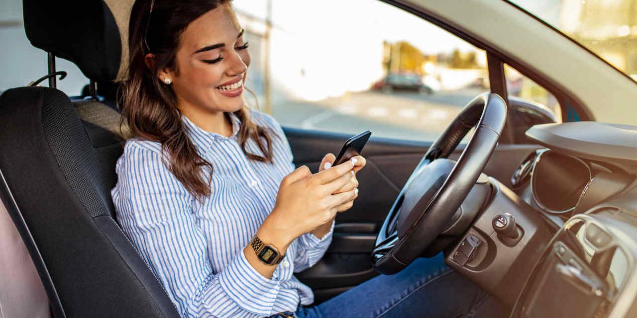 mulher dentro do carro parado mexendo no celular