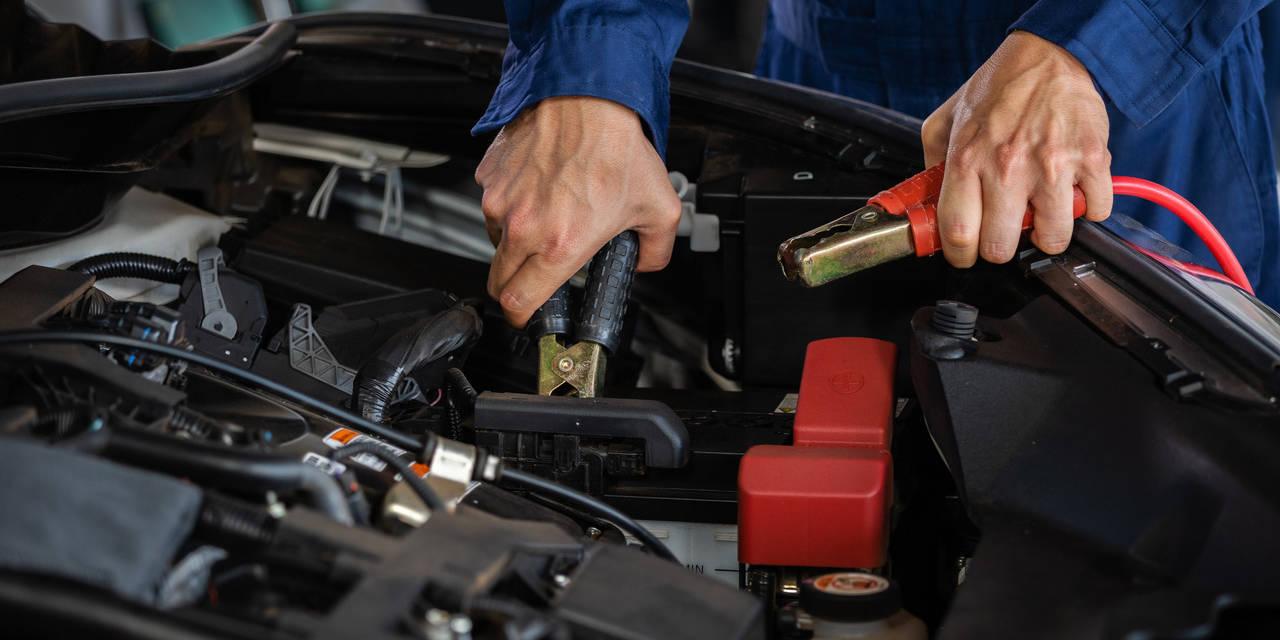 mecânico recarrega bateria com cabo de transmissão de energia