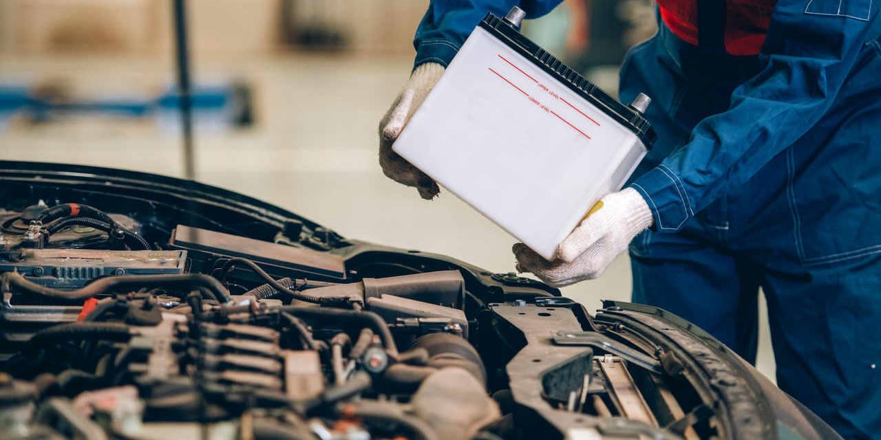 mecânico troca a bateria do carro