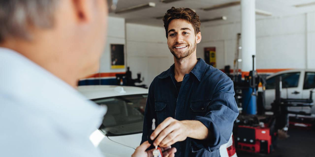 mecânico contente entrega chave do carro ao proprietário após concluir serviço