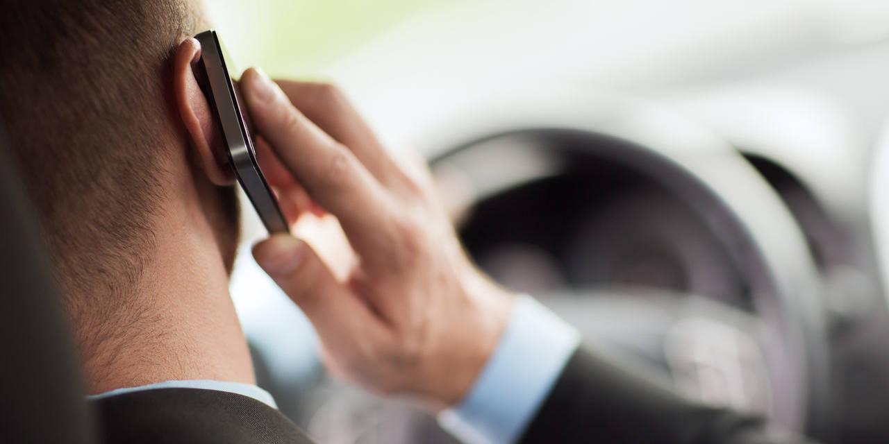 homem dirige enquanto fala no celular