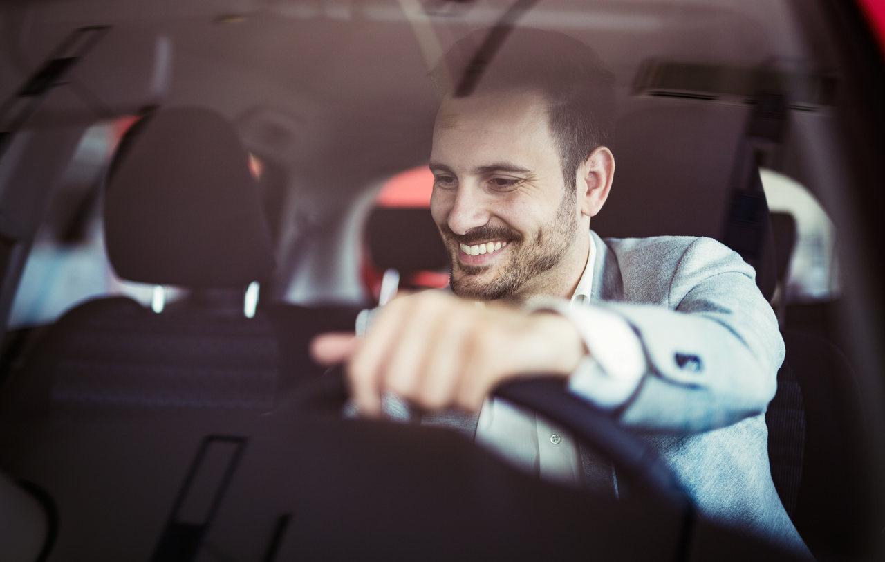 motorista sorridente dentro do carro