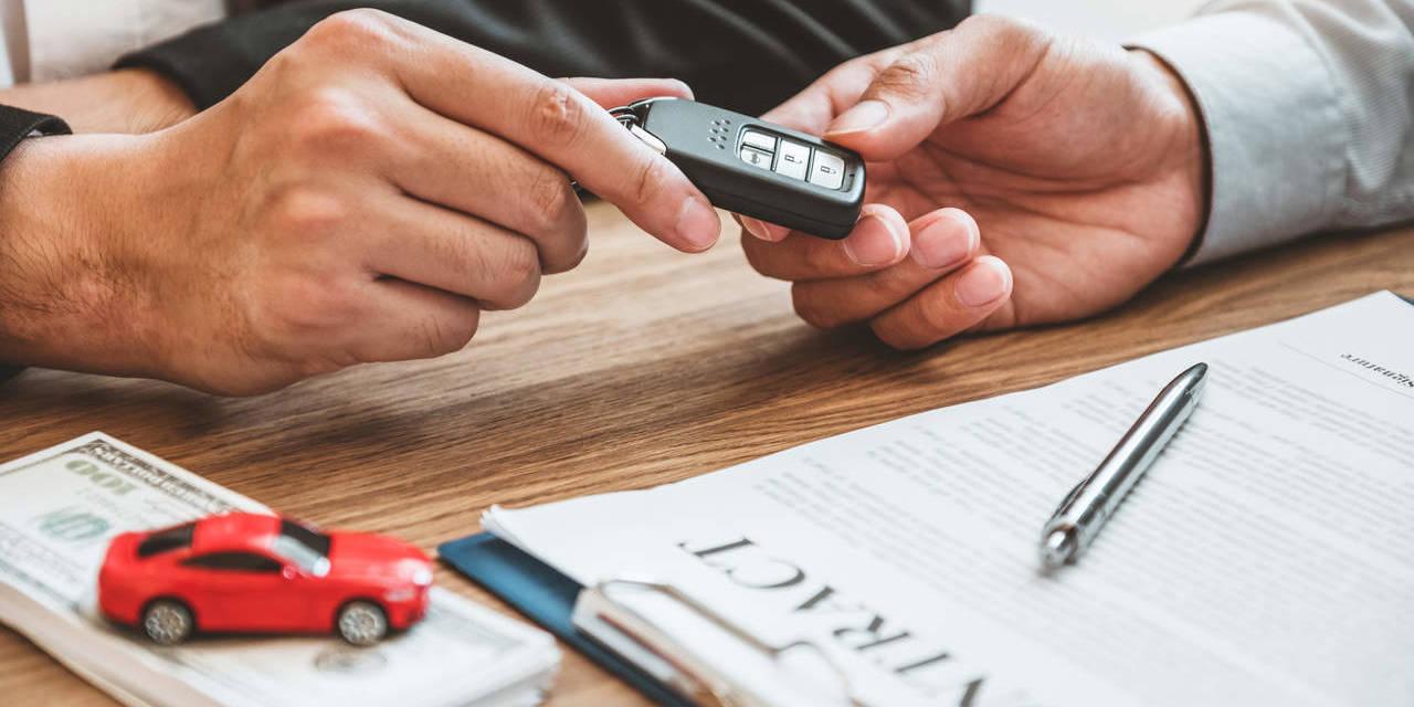 mão masculina segura chave de veículo após assinar contrato de aluguel de carro